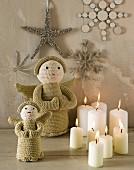 Weihnachtsdeko: Kerzen, gestrickte Engelsfiguren, an der Wand Sterne und Schneeflocken