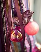 Silberner Vogel, pinkfarbene Kugeln und Bänder als Christbaumdeko
