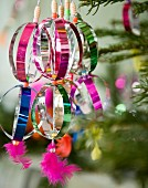 Colourful Christmas tree decorations made from shiny metal foil (close-up)