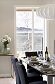 Black-upholstered chairs at set dining table below round pendant lamps with white lampshades in front of French windows with a view