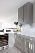 Corner of kitchen with white worksurface on grey-painted base units and wine chiller