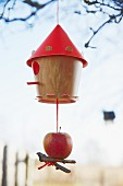 A bird house decorated with an apple