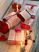 Christmas presents wrapped in red and decorated with little messages, decorative hearts and burning candles