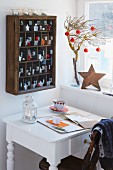 A wooden cabinet hanging on the wall as an advent calendar with a white desk in front of it