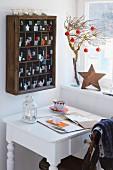 Holzvitrine an Wand als Adventskalender, davor weisser Schreibtisch