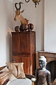 Hunting trophy above antique cupboard, Oriental sculpture and couch with animal-skin cushions