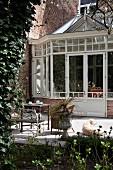 Traditioneller Wintergarten an Herrenhaus mit sonniger Terrasse und antiken Gartenmöbeln