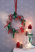 Festive wreath of pastry cutters and ribbons on wall above candlesticks