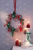 Kranz aus Plätzchenausstechern und Schleifenbändern als weihnachtlicher Wandschmuck, daneben Kerzenständern