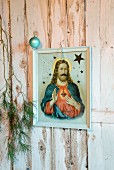 Framed icon, fir branches and Christmas bauble on white, rustic wooden wall