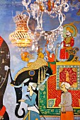 Chandelier in front of elephant caravan mural and crystal sconce lamp on wall