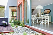Patio with wooden deck on pebbled floor, open, sliding terrace door and view of neo-antique dining set