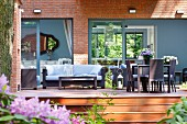 Dark, modern, wicker outdoor furniture on wooden deck in front of house with grey-painted window frames and wall elements in brick facade