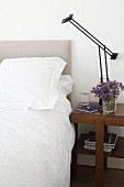 Designer Tizio lamp on antique side table next to bed with white bed linen and upholstered headboard