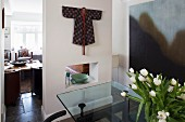 Kimono used as wall hanging on partition between dining area with glass table and living room