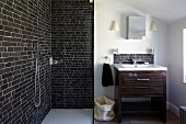 Open shower area with brick tiles and glass screen next to washstand with wooden base cabinet and small mirrored wall cabinet
