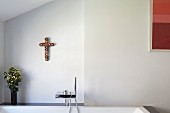 Ornamental cross on wall above bathtub with designer taps