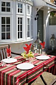 Table festively set with striped tablecloth on sunny terrace outside bay window of country house