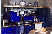 Loaf on table, vintage cooker and splashback in bold blue and cooking utensils hanging from hooks under white, wall-mounted shelf