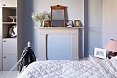 Teilweise sichtbares Bett mit Steppdecke, gegenüber Kaminsims mit Spiegel und Fotos in ländlich, modernem Schlafzimmer