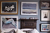 Framed pictures on pastel wall above sofa backrest