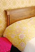 Ausschnitt eines Bettes mit Holz-Kopfteil, Blumenmuster auf Bettwäsche und Tapete an Wand