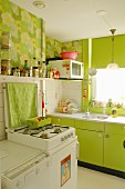 Spring atmosphere in fitted kitchen - lime green cupboard fronts and 70s-style floral wallpaper
