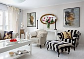 Bright, classic living room; glass-topped coffee table, ecru sofa and black and white striped armchair with matching footstool