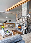 Back of sofa with grey marl cover, low coffee table made from white-painted pallet on castors and fireplace in gabion cage in modern interior
