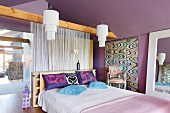 Bedroom with purple walls, double bed and white, string curtain used as partition