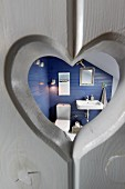 Heart-shaped cut-out in grey wooden door with view into bathroom with blue-painted walls