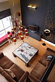 Brown sofa set and coffee table on parquet floor below chandelier with many small lampshades and black wall with sconce lamp