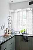 Kitchen with dark worksurface on L-shaped counter and integrated sink below window with crocheted curtains