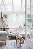 Blick durch offene Tür auf rundem Häkelteppich, Sessel und Sofa im Fiftiesstil in hellem Zimmer mit Verglasung