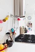 A white kitchen work surface with a gas hob with kitchen utensils and a string of lanterns hanging on the wall