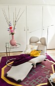 White fitted wardrobes, designer furnishings and pastel woollen rug in feminine interior