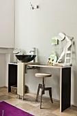 Black designer sink on MDF washstand and welded swivel stool in minimalist interior