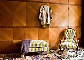 Raumhoher Einbauschrank mit Edelholzfurnier und antiker Armlehnsessel mit gelb gestreiftem Polsterbezug, Kleiderbank und Hund; eklektisches Flair