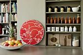 Pastell olivgrünes Küchenregal mit sortierten Gewürzbehältnissen und Teedosen neben rotem Kunstobjekt und Obstschale in offenem Wohnambiente