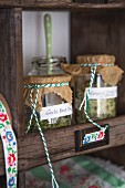 Home-made herb salts in preserving jars on dresser shelf