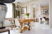 Verschiedene Stühle um massiven Holz-Esstisch mit Schnitzereien in traditionellem Esszimmer, offene Flügeltür und Blick ins Arbeitszimmer