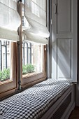Window seat with cushion on top of radiator cover in niche of window in period apartment