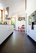 Lowdown view of a modern kitchen between the kitchen surface and built in appliances with dining area and red chairs in the background