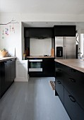 Free-standing counter in kitchen with black fitted cupboards