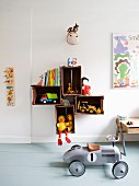 Retro, ride-on toy car on grey wooden floor and toys and books in and on wooden crates mounted on wall