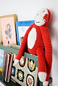 Crocheted toy monkey and books on shelf