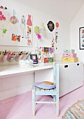 Wooden chair with peeling paint at desk in girl's bedroom with pink wooden floor