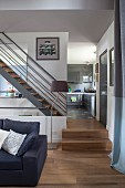 View from elegant living room to steel staircase with wooden treads; fitted kitchen with grey glossy fronts in background