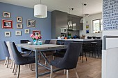 Open-plan kitchen-dining area in elegant shades of blue and grey decorated with family photos