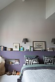 Modern bedroom with lilac headboard wall, stacked books, black and white pillows and vintage tailors' dummy